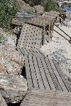 Hinter dem kleinen Hafen von Agios Ioannis  führt dieser Brettersteg zum benachbarten Sandstrand